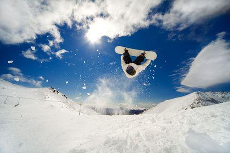 BACKFLIP: Snowboarder going off jump doing a backflip