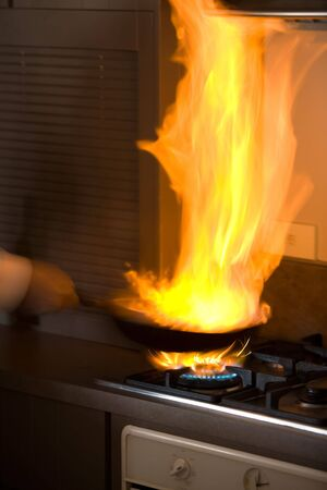 Chef in kitchen cooking in pan with big fire photo