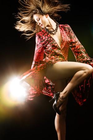 Fashion model in red dress on black studio background