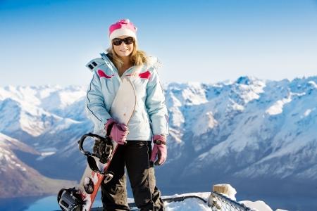 ski�r: Vrouw bedrijf snowboard met bergen op de achtergrond Stockfoto