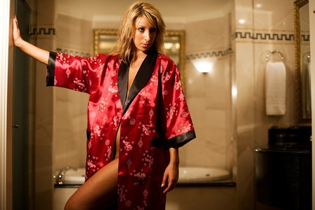 Woman in red bath robe gets ready for luxury bath Stock Photo - 4360038
