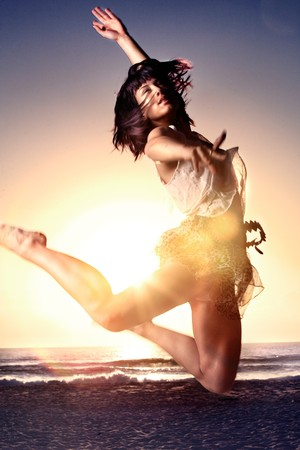Asian girl jumps high on beach with sun in background Banco de Imagens