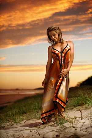 Fashion model on beach at sunset