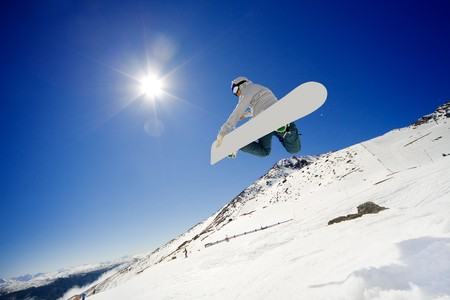 Snowboarder jumps in air with blue sky background Banco de Imagens