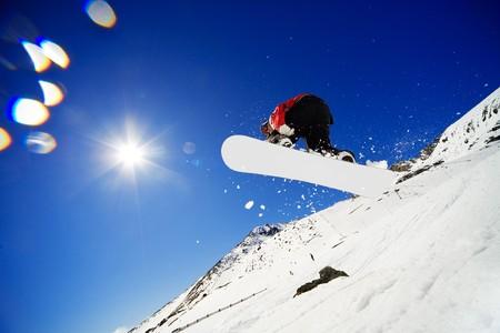 Snowboarder saltos en el aire con el cielo azul de fondo