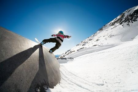 Snowboarder montar en la pared con el cielo azul de fondo