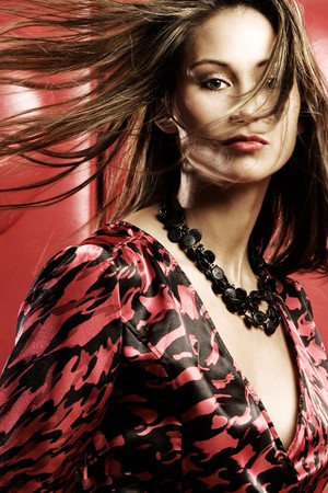 windblown: Young woman in studio with windblown hair in red dress Stock Photo