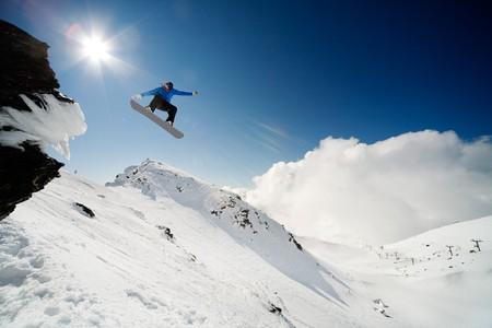 Snowboarder jumping through air from rock drop Banco de Imagens