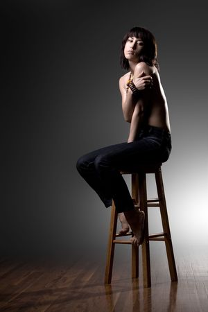 Lonely Asian girl sits on stool in studio Stock Photo - 6450743