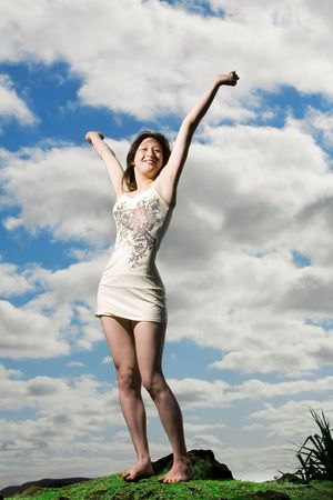 arms above head: Happy girl raises arms above head with sky in background