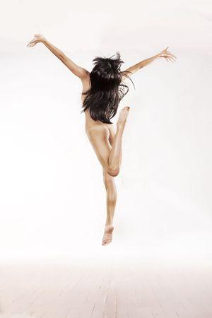 ni�a desnuda: Chica desnuda salta en el aire sobre fondo de estudio de whtie Foto de archivo