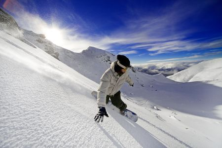 Snowboarder doing a toe side carve with deep blue sky in background Stock Photo
