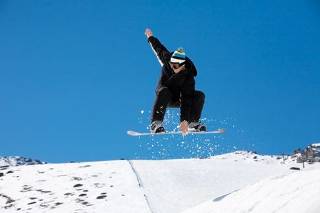 snowboarder jumping: Snowboarder jumping through air on blue sky background