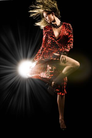 Beautiful girl in red dress dances on black studio background Stock Photo - 6632205