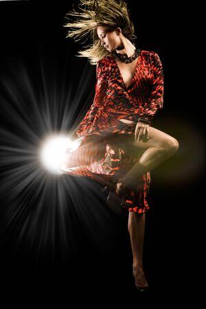 Beautiful girl in red dress dances on black studio background Stock Photo - 6632205