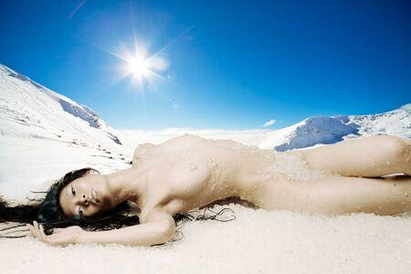 Bella ragazza nuda depone nel mucchio di neve e ghiaccio sulla montagna