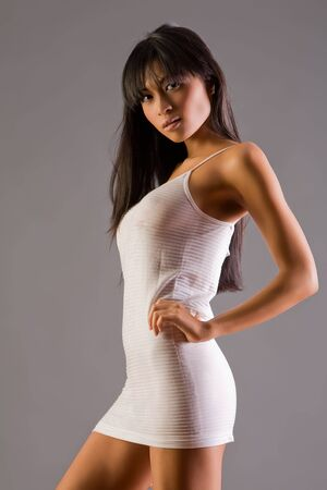 Beautiful Asian woman in slinky dress on grey background photo