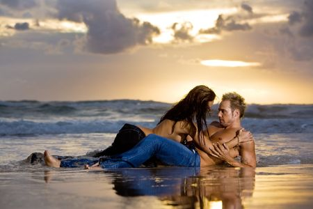 Young sexy couple on beach with sun rising in background