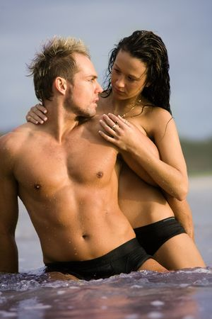 Young sexy couple playing in water on beach photo