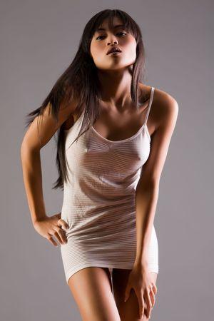 slinky: Beautiful Asian woman in dress on grey background