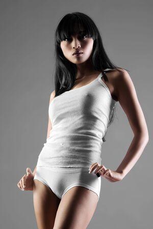 slinky: Beautiful Asian woman in slinky dress on grey background Stock Photo