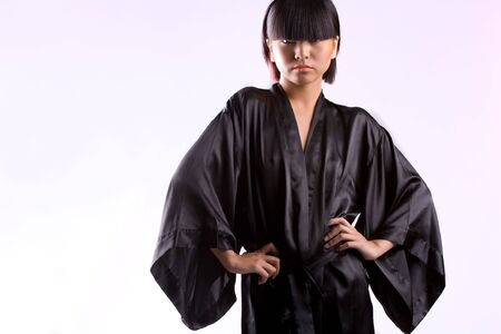 a white robe: Beautiful Asian girl in black robe on white studio background