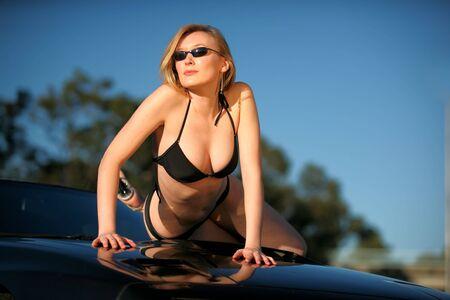 Beautiful blonde woman in bikini poses on sports car photo