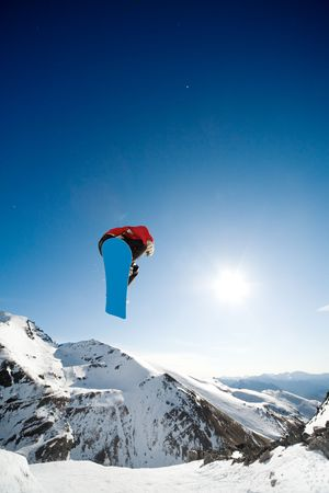 Snowboarder jumping through air on blue sky background photo