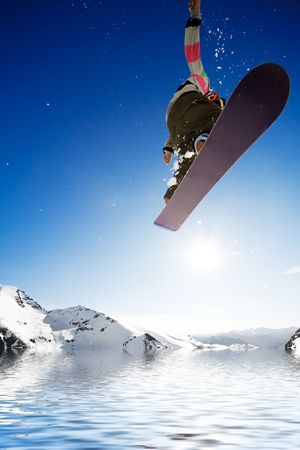 Crossover snowboard, surfing with boarder jumping into water