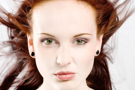 wind blown hair: Face shot of redhead model with green eyes