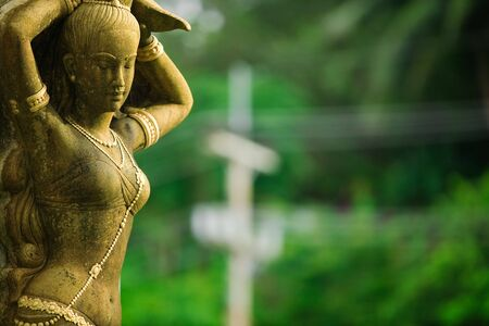Statue of woman with green trees in background Stock Photo