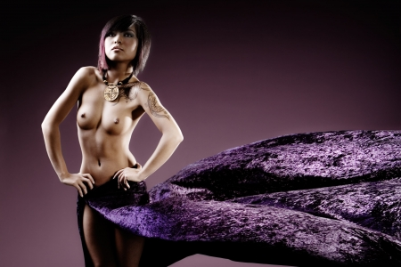 Asian fashion model topless in studio with flowing purple skirt