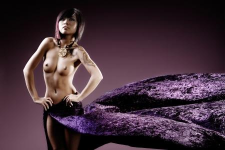beaux seins: Modèle de manière asiatique topless en studio avec découlant pourpre jupe  Banque d'images