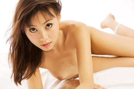 Beautiful Asian woman lays on white bed