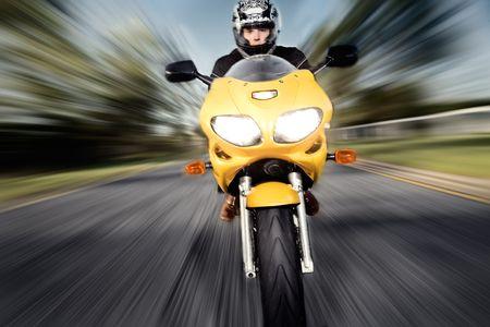 Conductor de la moto con el movimiento de desenfoque en segundo plano  Foto de archivo