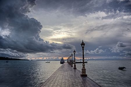 Pier leading into ocean with storm clouds in background photo