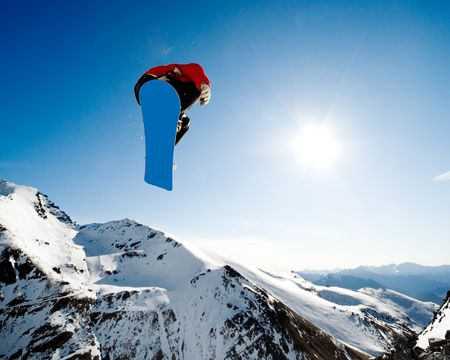Snowboarder jumping through air on blue sky background