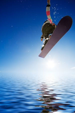 Crossover snowboard, surfing photo with boarder jumping into water photo