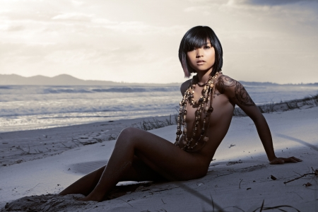 Beautiful Asian girl naked on beach wearing lots of beads Stock Photo - 7157512
