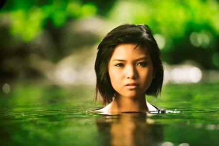 Beautiful Asian girl rises up out of stream