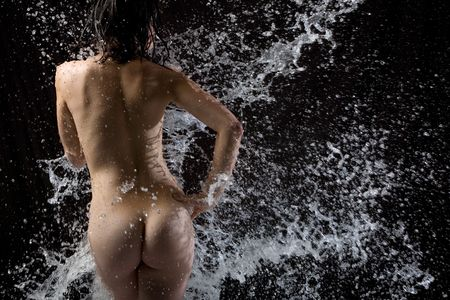 Naked body with water splashing over it Stock Photo