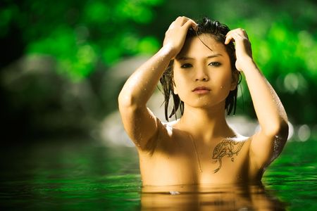 Beautiful naked Asian woman rises up out of water Stock Photo