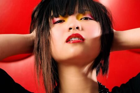Asian model with colorful makeup on red studio background photo