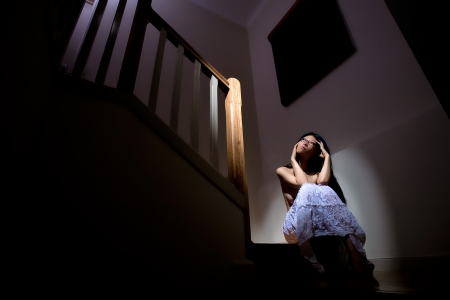 lonely person: Beautiful girl sits alone on stairs in dark house