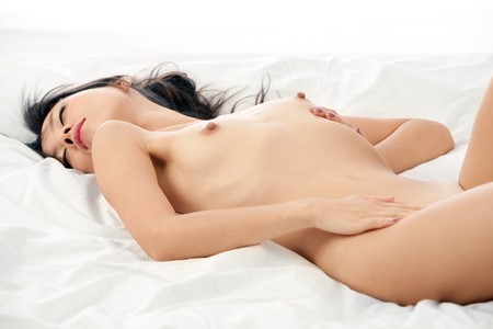 Nude woman lays on bed dreaming  Stock Photo