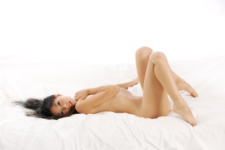 Nude Asian woman lays back on bed