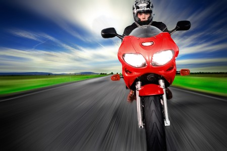Motorcycle moving very fast along motion blurred road photo