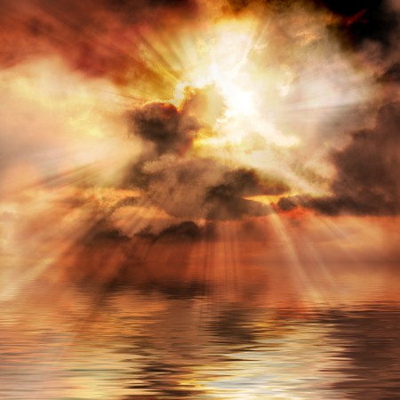 Spectacular sunrise bursts through clouds over water Stock Photo