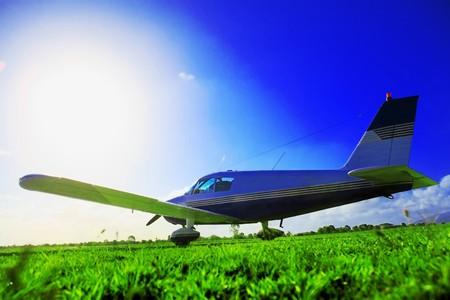 passtime: Small plane waiting on grassy field Stock Photo