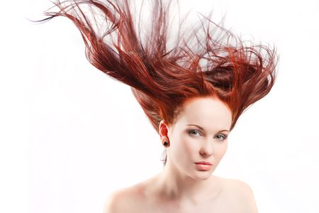 Beautiful woman with windblown red hair on white studio background Stock Photo